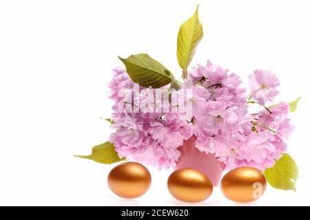 Rosado y dorado. Huevos de colores y sakura japonesa claro en ramo aislado sobre fondo blanco, espacio de copia. Concepto de Pascua y regalo