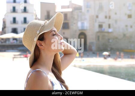Cerca de una joven hermosa mujer con sombrero disfrutando del sol en la playa. Vacaciones relajantes tomando el sol en Cefalu, Sicilia.