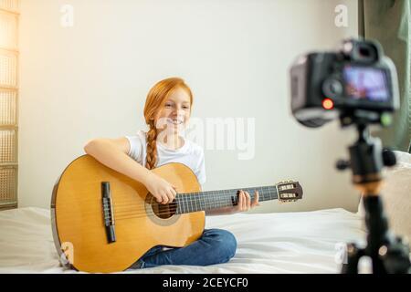 retrato de la hermosa niña caucásica blogger tocando la guitarra en la cámara. adorable chica sentada mostrando, realizando nueva melodía para los suscriptores. vl