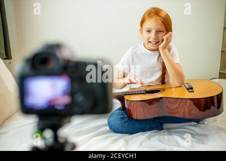lindo niño adorable blogger tocar la guitarra, hablar con la cámara cómo aprendió a tocar la guitarra acústica, ella es autodidacta