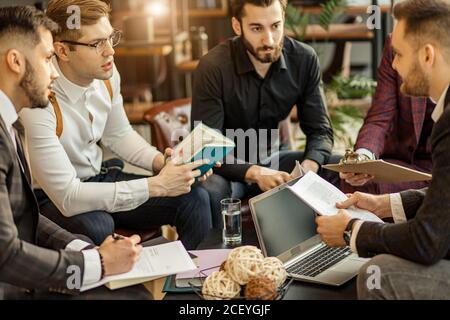 compañeros de trabajo de jóvenes caucásicos en el cargo se reunieron para discutir ideas de negocios, compartir experiencias y opiniones, cooperación exitosa Foto de stock