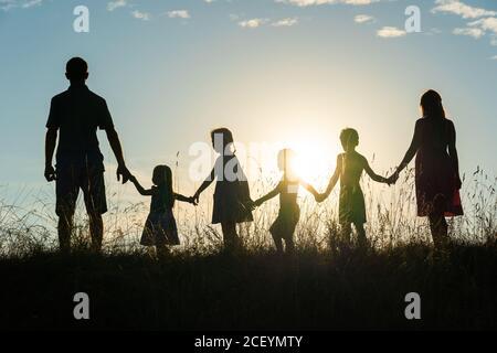 Silueta de una familia grande feliz al atardecer.