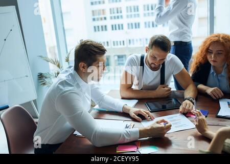 Jóvenes colegas, socios comerciales caucásicos que trabajan como diseñadores se sientan juntos en la mesa en la oficina moderna con ventana panorámica. Papeles, color penc