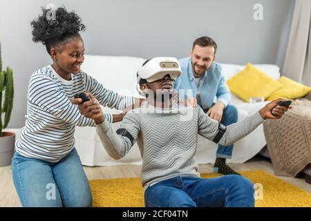 Sorprendido shoked sorprendido hombre africano llevaba gafas de realidad virtual mientras dos diversos amigos multirracial sentado en el sofá y sonriente