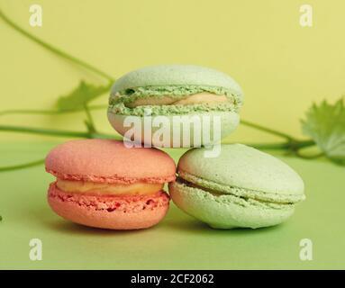 tres macarons horneados multicolor redondos, el postre se encuentra uno encima del otro sobre un fondo verde, de cerca.