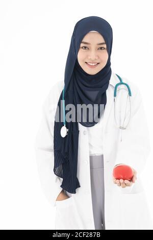 Joven adulto asiático atractiva mujer musulmana doctor usando hijab de pie con estetoscopio y manteniendo el corazón rojo aislado en fondo blanco. Foto de stock