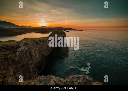 Vista panorámica de enormes acantilados rocosos sobre aguas onduladas contra el cielo del atardecer, Asturias, España