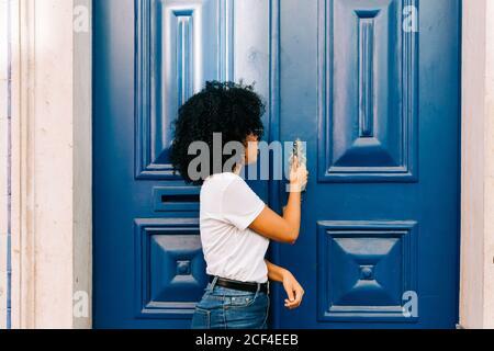 Mujer bastante étnica en camiseta blanca y vaqueros tocando azul puerta mirando hacia fuera Foto de stock