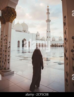 Vista posterior de la mujer islámica anónima en vestido negro largo caminando en la plaza de azulejos de la majestuosa mezquita blanca, Dubai