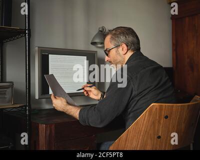 Hombre trabajando en el escritorio de casa con el ordenador a través de Internet de revisión proyectos de ley e informes