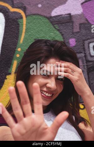 Mujer joven tocando la frente y sonriendo mientras está de pie cerca de colorido graffiti en el muro y pidiendo no tomar fotos en la ciudad calle