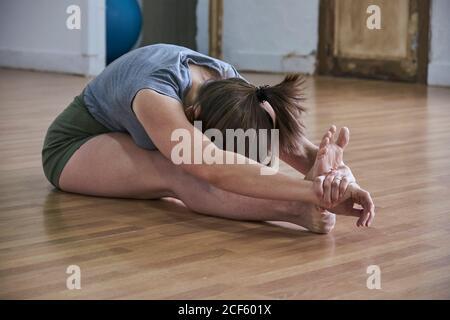 Mujer de ajuste relajado con los ojos cerrados realizando la curva hacia adelante sentada durante el entrenamiento de yoga en un amplio estudio
