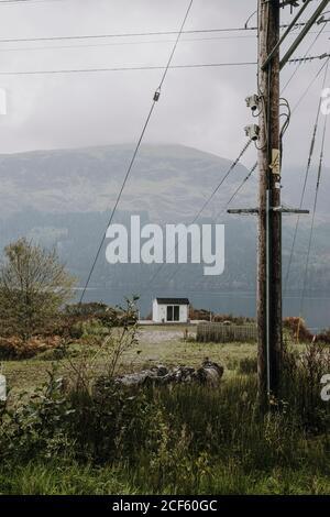 Paisaje rural escocés sombrío con casa blanca solitaria situada cerca lago de montaña en día nublado con polo eléctrico y cable en primer plano Foto de stock