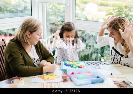 Mujer de mediana edad con niña y hija adulta teniendo diversión y juego de mesa creando imagen con mosaico colorido piezas mientras se sienta en la mesa redonda en la terraza