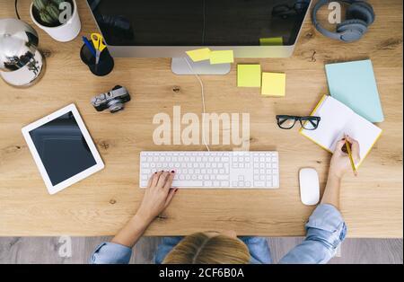 Vista superior de la mujer blanca rubia anónima sentada sobre madera escritorio escribiendo en un portátil y trabajando en un ordenador en una oficina doméstica moderna