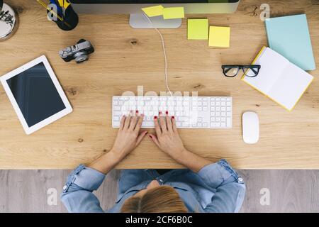 Vista superior de la mujer rubia caucásica anónima en ropa informal sentado en un escritorio de madera trabajando en un ordenador en un oficina en casa moderna