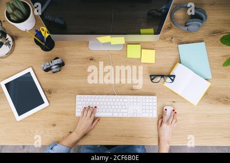 Vista superior de la mujer caucásica anónima recortada sentada en madera escritorio trabajando en un ordenador en una oficina doméstica moderna