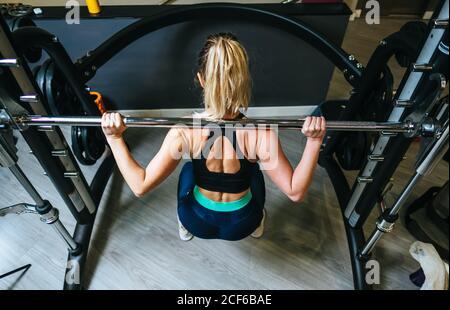 Mujer levantamiento barbell en gimnasio
