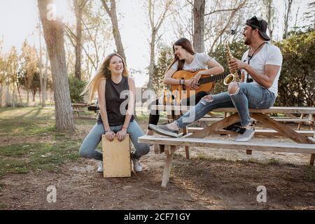 Joven y mujer con instrumentos musicales sentados cerca de la mesa y riendo en el día soleado en el parque