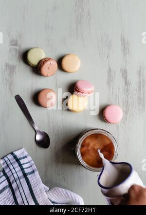De arriba persona anónima vertiendo leche en taza de café cerca de un montón de coloridos macarrones y cuchara con servilleta mesa blanca