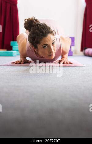 Vista lateral de la morena concentrada deportiva flexible en la práctica de sportswear acostarse yoga pose sobre la alfombra