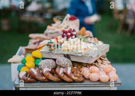 Bandeja de madera con canapés colocados en la bandeja con galletas y. frutas en el bar de dulces servido durante la ceremonia de boda al aire libre Foto de stock
