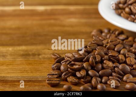 Día internacional del concepto de café. Primer plano taza de café blanco llena de granos de café.