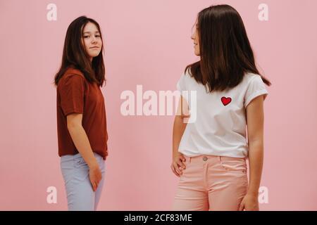 Dos pequeñas hermanas gemelas felizmente sonriendo, mirando diferentes direcciones