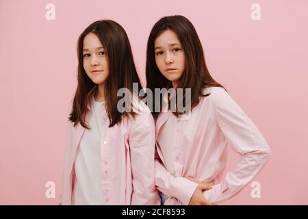 Hermosas hermanas gemelas posando, de pie una detrás de la otra. Sobre rosa