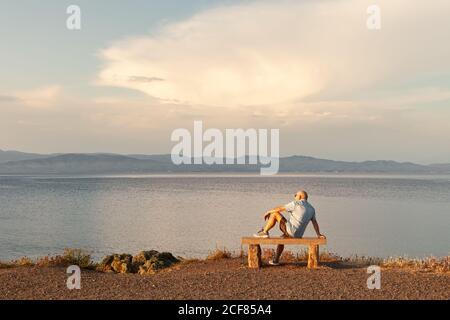 Vista posterior de un anciano sentado en un banco y disfrutando de un tranquilo paisaje marino al atardecer, Halkidiki, Grecia Foto de stock