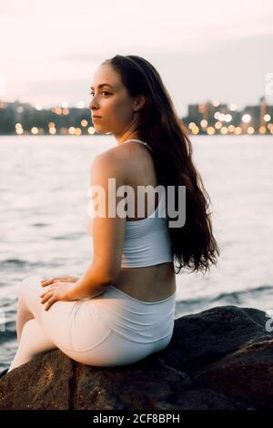 vista lateral de mujer concentrada en activewear sentada sobre piedra en la orilla mientras practica yoga en el fondo de la noche paisaje urbano y mirando lejos