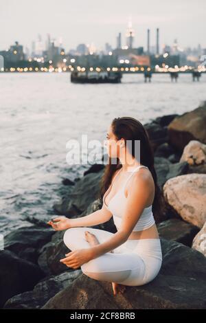 Desde arriba vista lateral de mujer concentrada en la sesión activa sobre la piedra en la orilla mientras practica yoga en el fondo de por la noche, paisaje urbano y mirando lejos