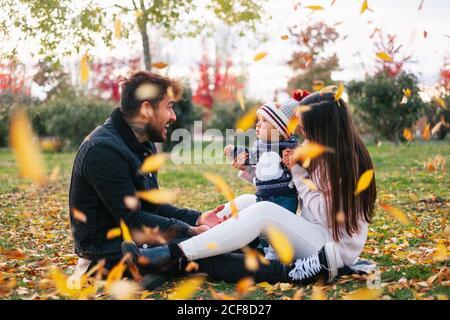 Vista lateral de joven alegre y mujer con lindo bebé sentado en la hierba y divertirse con amarillo sale mientras pasa tiempo juntos en el parque de otoño