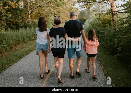 Vista posterior del hombre y la mujer adultos con las hijas vestidas en camisetas y pantalones cortos casuales caminando por el camino entre los árboles verdes mientras pasan el día de verano juntos en el campo