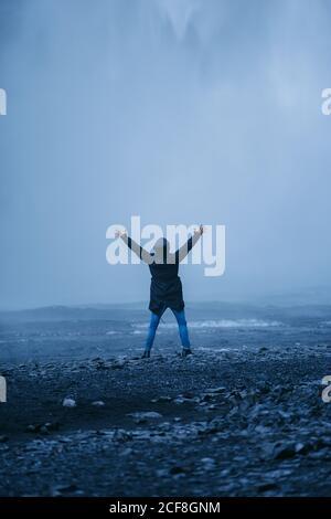 Vista trasera de un hombre de turismo inreconocible encantado en el exterior de pie con los brazos elevados en el fondo de la cascada mientras disfruta de las vacaciones En Islandia y mirando cámara