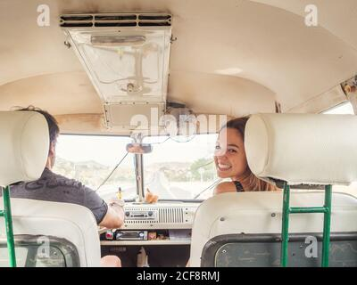 Vista posterior de hombre irreconocible conductor y joven mujer sonriente sentado frente al coche mirando la cámara