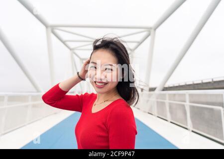 Encantadora dama asiática en camisa roja sonriendo y mirando cámara mientras camina por el moderno puente de la ciudad