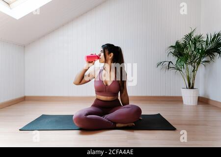 Joven mujer atlética en sportswear sentado en la estera y beber el agua mientras descansa durante la sesión de yoga en la sala de luz moderna
