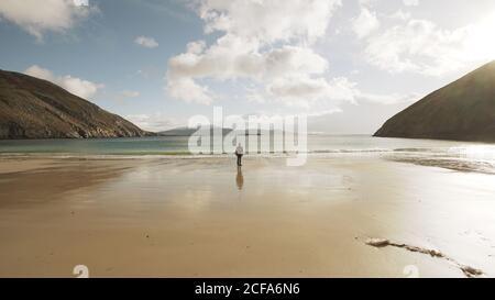 Hombre turístico contemplando la naturaleza tranquila paisaje oceánico mientras se está de pie Playa de arena en la costa de Irlanda