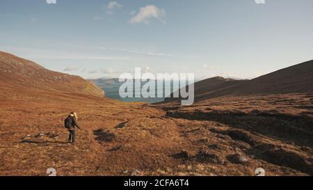 Vista posterior de una mujer irreconocible caminando por un maravilloso paisaje natural Y el mar mientras se encuentra en un acantilado en Irlanda mirando hacia fuera