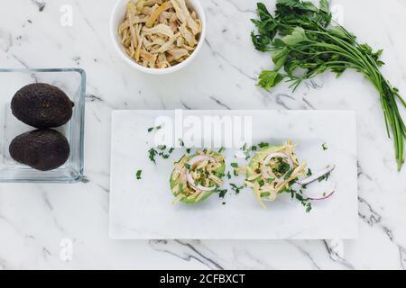 Desde arriba de ensalada de pollo servida con cilantro y cebolla en las mitades del aguacate maduro sobre la superficie de mármol blanco Foto de stock
