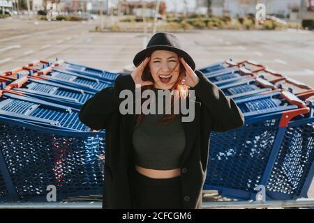 Atractiva mujer joven con pelo rojo en sombrero negro y. chaqueta gestuando y gritando en el estacionamiento con