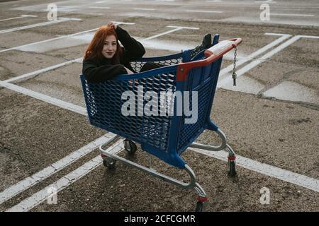 Mujer joven atractiva con pelo rojo en chaqueta negra teniendo diversión sentado en el carrito de compras en el estacionamiento marcado