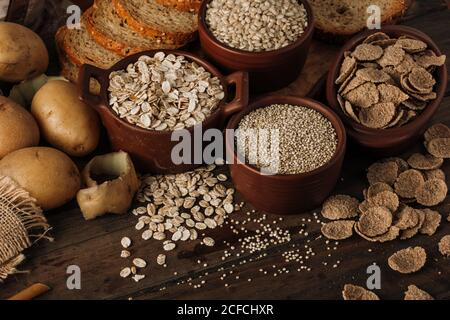 De arriba cereales semillas de avena en tazones patatas y rebanadas pan sobre fondo de madera