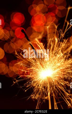 Quemando sparkler contra el bokeh dorado sobre fondo negro