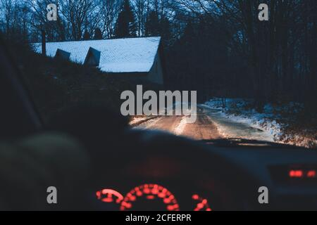 Mano de conductor anónimo que dirige el coche moderno a lo largo de la campiña estrecha camino en la noche de invierno en el pueblo Foto de stock