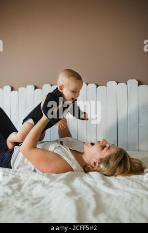 Vista lateral de la mujer joven excitado levantando lindo bebé y jugar mientras está acostado en una cómoda cama en casa Foto de stock