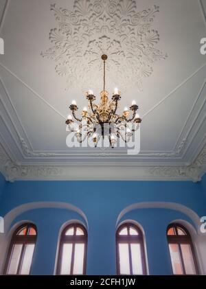 Hermosa araña dorada suspendida por un techo blanco ornamentado dentro de un palacio con paredes azules y ventanas arqueadas. Diferentes formas geométricas, Foto de stock