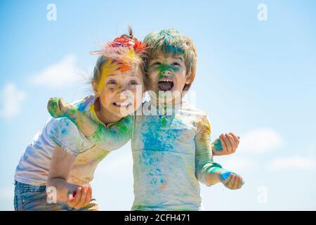 Niños felices jugando con polvo de holi de color. Divertidos y lindos niños preescolares mirando la cámara mientras abrazan.