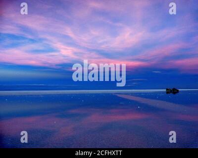 Mágico azul rosa puesta de sol. Reflejo del cielo coloreado al atardecer en el lago salado. Salinas de Salar de Uyuni, Bolivia. Romántico paisaje nocturno.